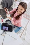 Top view of upbeat girl reviewing new powder. Best product. The top view of an upbeat pre-teen girl showing a new powder and a new makeup brush and reviewing Royalty Free Stock Photo