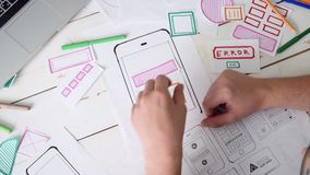 Top view of UX designer creating smartphone application layout stock video