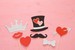 Top view Valentine& x27;s day background with funny photo booths props: gentleman hat, mustache, heart with arrow and crown. Top view Valentine& x27;s day stock images