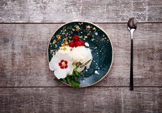 Top view of a vanilla ice cream on a plate and a spoon. Ice cream with a flower. Sweet dessert on a wooden background. Copy space. Royalty Free Stock Image