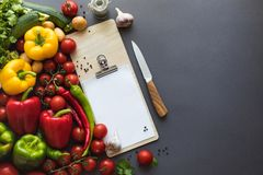 Top view of various fresh ripe vegetables with blank clipboard, cutting board and knife. On grey Stock Photo