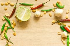 Top view of various fresh vegetables Paprika, peanut, garlic, lemon and herbs isolated on Wood background royalty free stock images