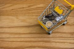 Top view of various money coins Baht in yellow mini shopping cart or supermarket trolley. Business and Financial Concept : Top view of various money coins Baht Royalty Free Stock Photo