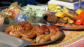 Top view on Various sausages, vegetables, Bulgarian pepper and other food cooked on the grill. Fresh Grilled food lie on the counter of a Street Market. A stock footage