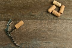 Top view, of various wine openers and red grapes. Top view, close up of single wine cork opener with four pulled corks forming a square and one cork on wine royalty free stock image