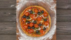 Top view of vegetarian pizza eating on wooden plate, stop motion animation