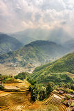 Top view of village houses and rice terraces of Sa Pa, Vietnam. Top view of village houses and rice terraces. Sapa District, Lao Cai Province, Vietnam. Rays of Royalty Free Stock Photo