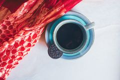 Cup of coffee and a red scarf on white marble background royalty free stock images