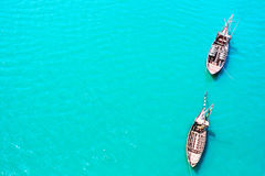 Top view of vintage boats in cyan blue transparent sea water Stock Photos
