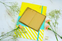 Vintage book with empty sheets,brigt paper folder and flowers on a marble background. Top view vintage book with empty sheets,brigt paper folder and flowers on a royalty free stock photos