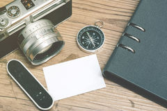 Top view of vintage camera,compass,surfboard and planner book layout on wooden floor. Stock Images