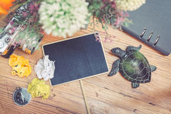 Top view of vintage camera, crumple paper,compas and planner book layout on wooden floor. Royalty Free Stock Photos