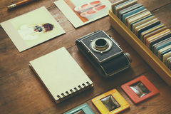 Top view of vintage camera and old slides frames over wooden table background Stock Photography