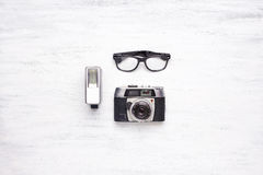 Top view of vintage camera on a white wooden background. Top view of vintage camera and hipster glasses on a white wooden table with copyspace Stock Image