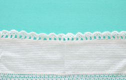 top view of vintage hand made beautiful fabric with crochet over pastel mint wooden background. Stock Photo