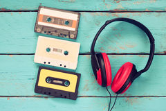 Top view of vintage headphones and cassettes over aqua wooden table. retro filtered Royalty Free Stock Photography