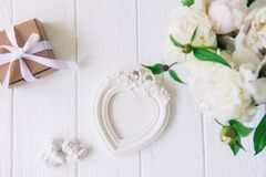 Top view vintage heart shaped photo frame, statuette of two antique lovely angels, giftbox and white peonies bouquet on the wooden. Table. Love background royalty free stock photo