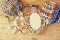 Top view of vintage nautical frame from ropes, wooden boat and natural seashells on wooden table Stock Image