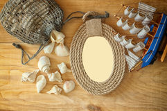 Top view of vintage nautical frame from ropes, wooden boat and natural seashells on wooden table.  Royalty Free Stock Image
