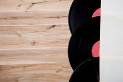 Top view of vinyl records over wooden table. Royalty Free Stock Image