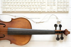 top view of violin earphone and computer keyboard Royalty Free Stock Photos