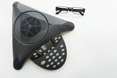 top view of voip IP conference phone with eye glasses on meeting table Royalty Free Stock Photo