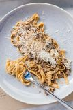 Top view of Wagyu Ragu with Tagliatelle pasta topping with cheddar cheese. Rolled spaghetti with fork.  Royalty Free Stock Image