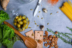 Top view of walnuts, bread, spices and salad on a gray background. Pasta with organic ingredients. Cooking concept. stock image