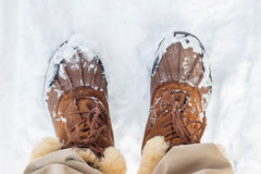 Top view in warm man brown boots with fur on white snow. Royalty Free Stock Image
