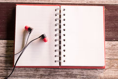 Top view and warm tone. earphone putting on empty notebook red c Stock Image