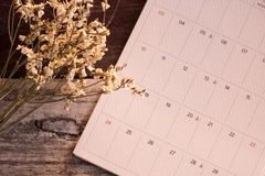 Top view and warm tone. white bouquet flower putting beside cale. Top view and warm tone. white bouquet flower putting beside white calendar page on wooden are Royalty Free Stock Image