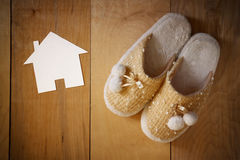 Top view of warm woman slippers over wooden floor and paper house shape as welcome home concept Royalty Free Stock Images