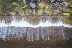 Top view of water diversion dam. Water diversion dam on a mountain river - aerial overhead view stock photo