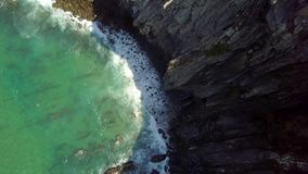 Top view of waves dashing against rocks. From above aerial view of turquoise ocean waves splashing against coast cliffs making white foam under bright sunlight stock video footage