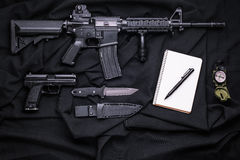 Top view on the weapon, compass and notepad. Rifle, gun, knife with sheath, compass and notebook with pen on on black cloth,top view stock photos