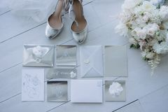 Top view of wedding invitations with bridal shoes and bouquet. On floor stock photography