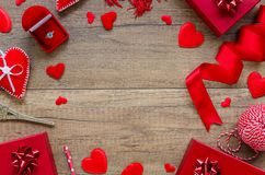 Top view wedding proposal concept. Romantic border arrangement with hearts, red ring box on a wooden background. Copy stock image