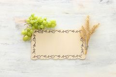 Top view of wheat crops and green grapes over white wooden background. Symbols of jewish holiday - Shavuot.  stock photography