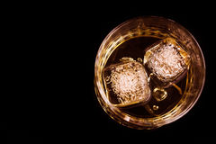 Top of view of whiskey in the glass with ice cubes on black background, focus on ice cubes Stock Images