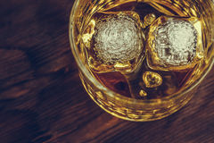 Top of view of whiskey in glass with ice cubes on wood table background, focus on ice cubes Royalty Free Stock Image