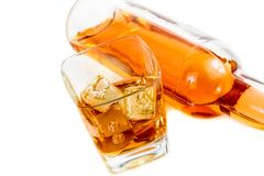Top of view of whiskey near bottle on white background with reflection Stock Photos
