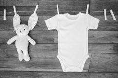 Top view white baby bodysuit on a clothesline with teddy hare on a wooden background. Copy space for text mockup