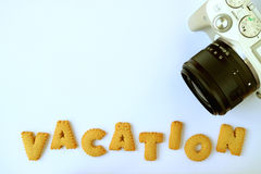 Top view of white and black camera with alphabet shaped biscuits, spelling the word VACATION, on light blue table Stock Image