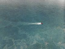 Top view of a white boat sailing in the blue sea stock images