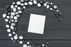 White book on a gray table. Top view of a white book with a blank cover lying on a gray wooden table inside a crescent made of pebbles. 3d rendering mock up Stock Photo
