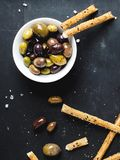 Top view of white bowl with black and green olives and bread sticks royalty free stock photography