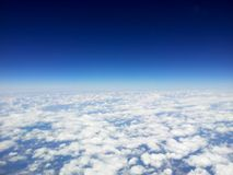Top view of white clouds from a airplane, on a background of the clear blue sky.  Stock Images