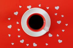 Top view of white coffee cup surrounded by white paper heart on red background. Stock Images