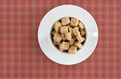 Top view of white coffee or tea cup full brown sugar cubes on red squared background. Diet unhealty sweet addiction Royalty Free Stock Photos