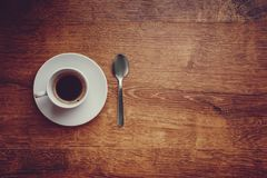 Top view of white Cup with black coffee on a white saucer and teaspoon on dark brown wooden background. With space for  copytext on the right Stock Photos